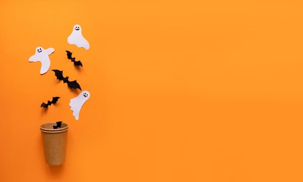 Composição plana de halloween de abóbora laranja, morcegos pretos, elenco de papel branco