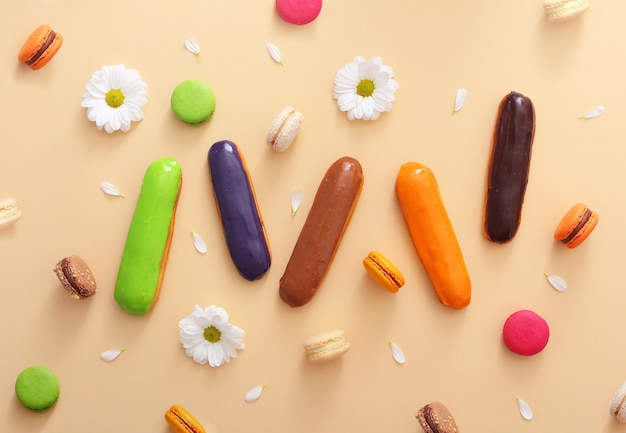 Composição plana de macaroons franceses coloridos, éclairs, flores brancas e pétalas