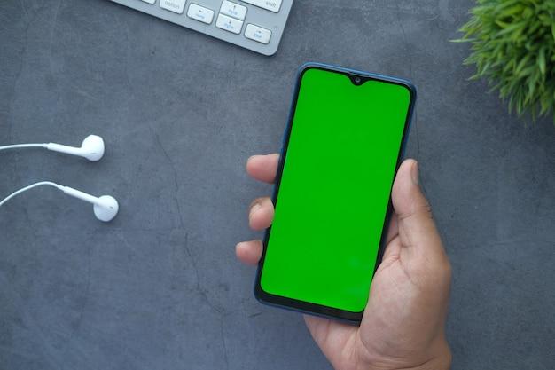 Composição plana de mão segurando o telefone inteligente no preto