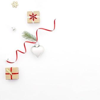 Composição plana de natal leigos sobre fundo branco, com caixas de presente de feriado, um brinquedo em forma de coração e ramos de abeto. conceito de natal, minimalismo, férias, venda.
