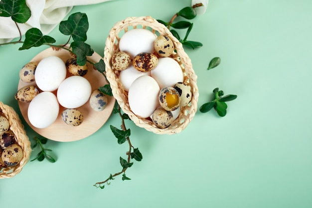 Composição plana de páscoa com folhas verdes e ovos de páscoa em um fundo verde