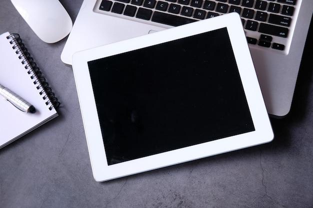 Composição plana de tablet digital, laptop e escritório estacionário em fundo preto