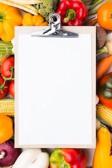 Composição plana e colorida de vegetais com prancheta