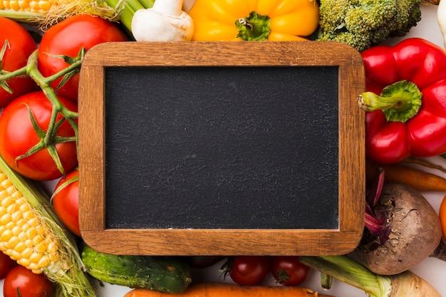 Composição plana e colorida de vegetais com quadro-negro