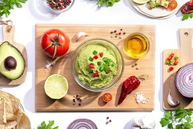 Composição plana lay. guacamole com ingredientes na placa de madeira em fundo branco.