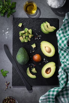 Composição plana leiga com abacates frescos em fundo escuro.