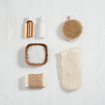 Composição plana leiga com acessórios de banho com pequenas garrafas com gel e xampu, sabonete, sal marinho, pano de rosto na mesa de madeira branca.