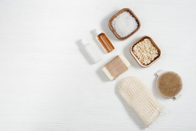 Composição plana leiga com acessórios de banho com pequenos frascos com gel e shampoo, sabonete, sal marinho, pano de rosto na mesa de madeira branca com espaço de cópia.