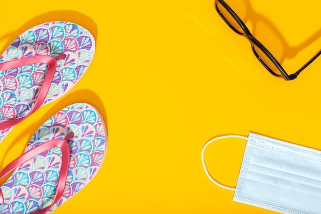 Composição plana leiga com acessórios de férias de verão e máscara facial em fundo amarelo