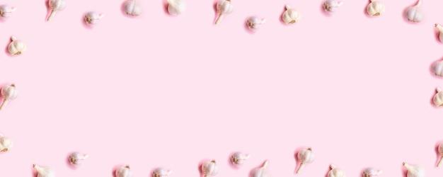 Composição plana leiga com alho em fundo rosa claro