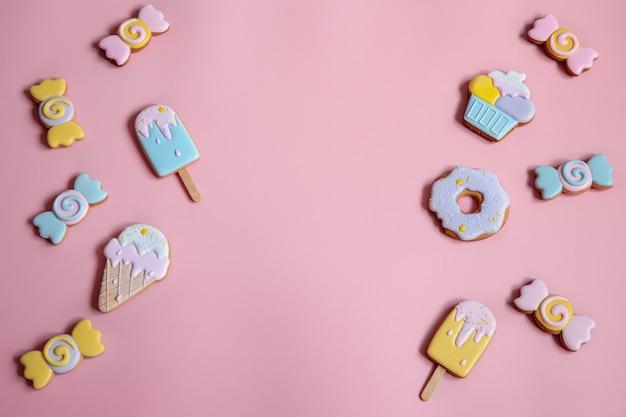 Composição plana leiga com biscoitos de gengibre vitrificados brilhantes no espaço da cópia de fundo rosa.
