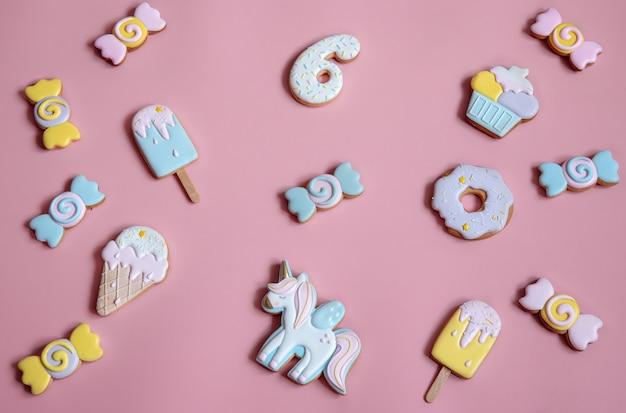 Composição plana leiga com biscoitos de gengibre vitrificados brilhantes sobre fundo rosa.