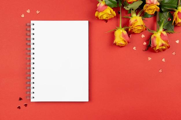 Composição plana leiga com caderno de papel espiral, corações e rosas no vermelho