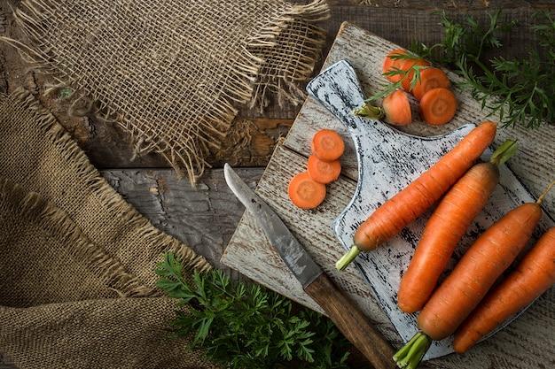 Composição plana leiga com cenouras no fundo rústico