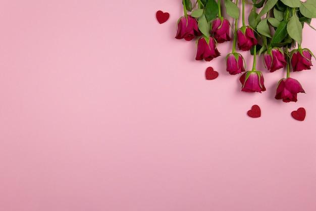 Composição plana leiga com corações e rosas vermelhas na rosa.