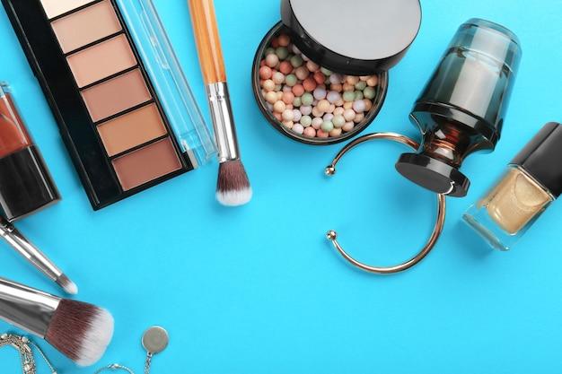 Composição plana leiga com cosméticos decorativos e acessórios em azul