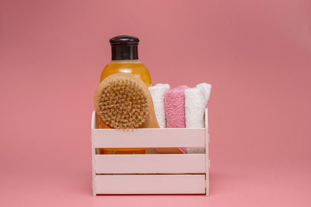 Composição plana leiga com cosméticos spa e toalha em fundo rosa.