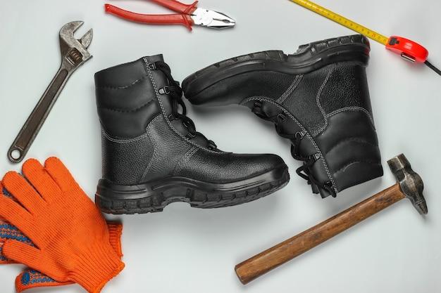 Composição plana leiga com diferentes ferramentas e instrumentos de trabalho industrial, equipmen de segurança em fundo branco. vista do topo