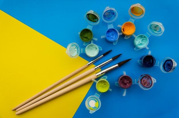 Composição plana leiga com diferentes tintas acrílicas ou óleo e escovas