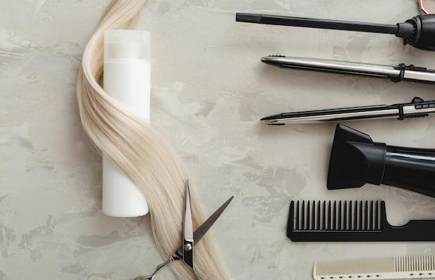 Composição plana leiga com ferramentas de cabeleireiro e frasco branco de produto cosmético, cabelo loiro em fundo cinza