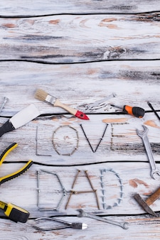 Composição plana leiga com ferramentas de construção em fundo de madeira