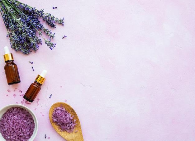 Composição plana leiga com flores de lavanda e cosméticos naturais em fundo rosa