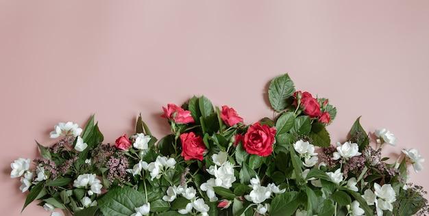 Composição plana leiga com flores frescas em fundo rosa.