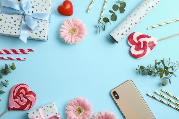 Composição plana leiga com flores gerbera, caixa de presente e doces em azul. espaço para texto