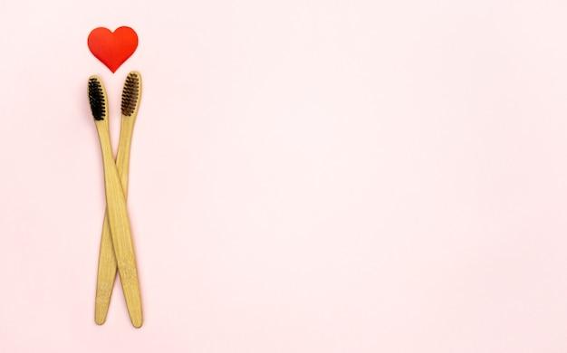 Composição plana leiga com formato de coração com escovas de dente de bambu e espaço para texto na parede rosa, vista superior. conceito de ecologia com estilo de vida saudável.