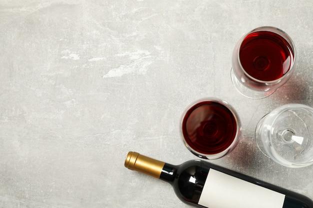 Composição plana leiga com garrafa e copos de vinho em cinza