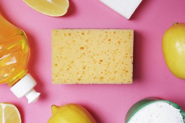 Composição plana leiga com limão, esponja, sabão, pó em um fundo rosa. espaço livre para texto. vista do topo.