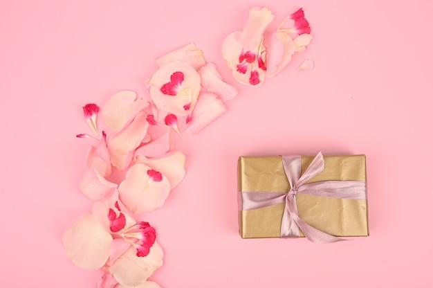 Composição plana leiga com lindas flores e caixa de presente no espaço rosa. espaço para texto
