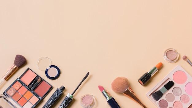 Composição plana leiga com maquiagem cosmótica em fundo laranja