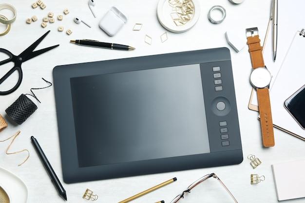 Composição plana leiga com mesa digitalizadora, artigos de papelaria e acessórios na mesa branca. local de trabalho do designer