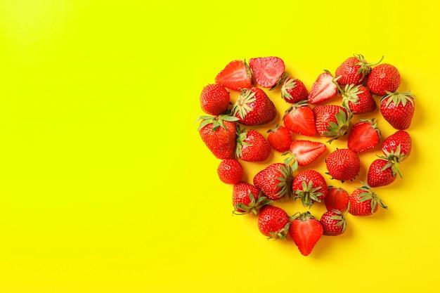 Composição plana leiga com morangos em forma de coração na cor de fundo, espaço para texto