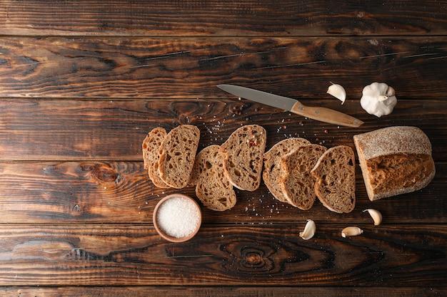 Composição plana leiga com pão fresco no espaço de madeira, vista superior e espaço para texto