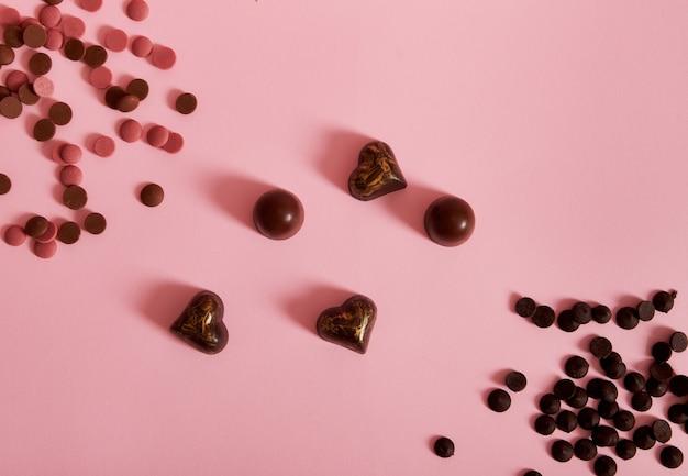 Composição plana leiga com pílulas de chocolate rosa e escuro espalhadas e trufas de chocolate e bombons na superfície rosa com espaço de cópia. conceito do dia do chocolate