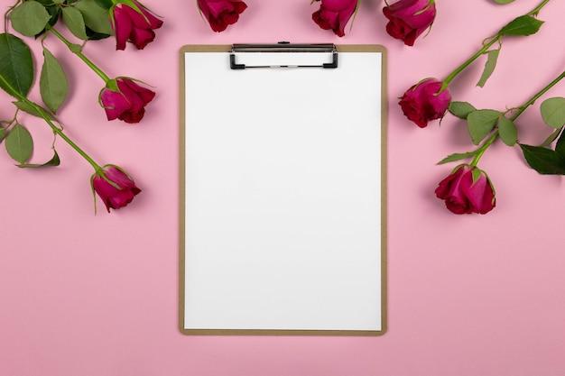 Composição plana leiga com prancheta e rosas na rosa.