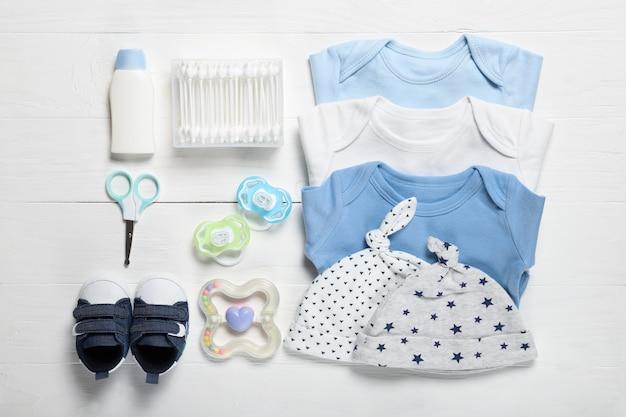 Composição plana leiga com roupas de bebê e acessórios em fundo de madeira