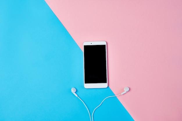 Composição plana leiga com smartphone, fones de ouvido em um fundo azul e rosa.