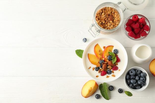 Composição plana leiga com sobremesa parfaits e ingredientes em fundo branco de madeira