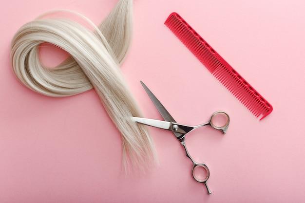 Composição plana leiga com tesouras de ferramentas de cabeleireiro, pentes e fios de cabelo loiro na superfície de cor rosa com espaço de cópia para o texto. serviço de cabeleireiro. serviço de salão de beleza.