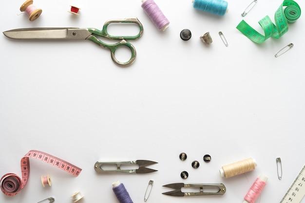 Composição plana leiga com tesouras e outros acessórios de costura em fundo branco. espaço para texto