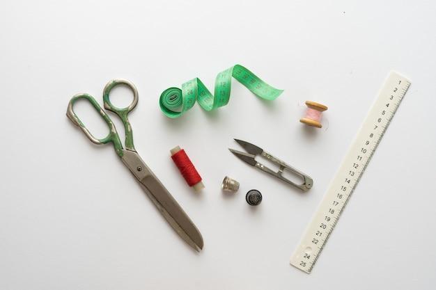 Composição plana leiga com tesouras e outros acessórios de costura sobre fundo claro.