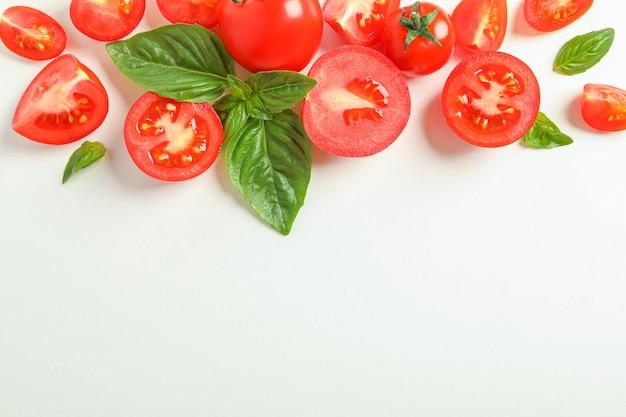 Composição plana leiga com tomate cereja fresco e espaço de manjericão para texto. legumes maduros