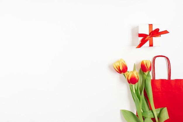 Composição plana leiga com tulipas amarelas vermelhas perto de um saco de papel vermelho com presente em um fundo branco com espaço de cópia. dia de valentin, aniversário, dia das mães