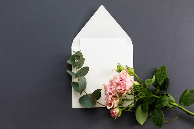 Composição plana leiga com um envelope branco, cartão em branco e uma peônia rosa flor sobre um fundo cinza. maquete para casamento ou dia dos namorados. vista do topo.