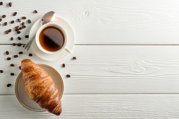 Composição plana leiga com uma xícara de café e um croissant em uma mesa de madeira branca com espaço de cópia.