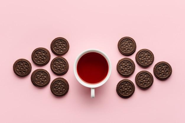Composição plana leiga com uma xícara de chá de hibisco e biscoitos de chocolate, isolados em uma parede rosa.