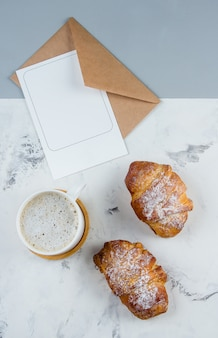 Composição plana leiga com xícara de café, croissants e limpo nota vazia para o texto em segundo plano.